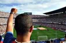 Un aficionado anima a su equipo en un campo de fútbol.