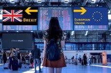 Mujer de espaldas frente a dos carteles mostrando la bandera del Reino Unido y otra de la Unión Europea.