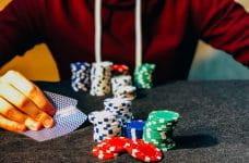 Una mano sostiene dos cartas de póker con fichas sobre una mesa.