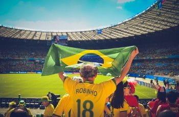 Un aficionado levanta la bandera de Brasil durante un partido de fútbol.