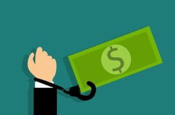 Una mano está esposada al símbolo del dólar.