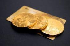 Tres monedas de Bitcoin sobre una tarjeta de crédito.