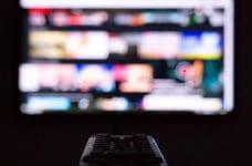 Un mando de televisión apuntando hacia una pantalla difuminada.