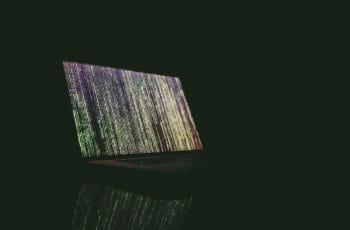 Un portátil con códigos verdes verticales en la pantalla.