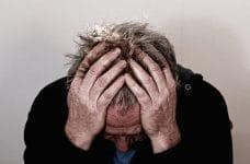 Un hombre de mediana edad se agarra la cabeza en señal de desesperación.