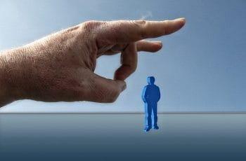 Un dedo a punto de golpear la figura de una persona.