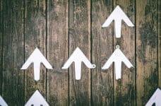 Varias flechas blancas apuntando hacia arriba sobre un fondo de madera.