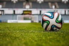 Un balón de fútbol en el césped de un estadio.