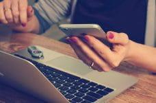 Una mano sujeta un teléfono móvil enfrente de un ordenador portátil.