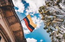 Una bandera de Colombia ondeando sobre un tejado.