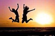 Dos personas saltando enfáticamente en una puesta de sol.