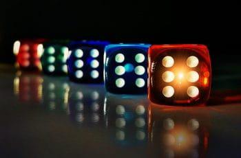 Dados de colores iluminados sobre una mesa transparente.