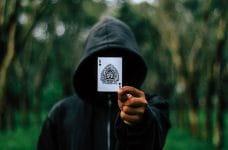 Una persona encapuchada muestra un as de picas.