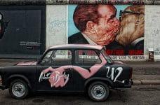 Fragmento pintado del muro de Berlín con un Trabant en primer plano.