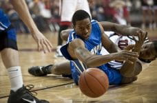 Dos jugadores de baloncesto se disputan un balón.