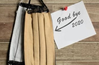 Dos mascarillas y un cartel en el que se lee Adiós, 2020.