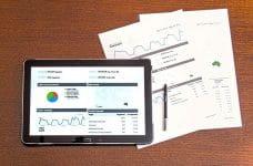 Tablet y hojas con gráficos sobre una mesa.