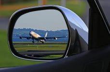 Avión despegando visto desde un espejo retrovisor.