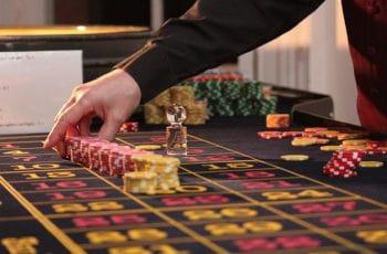 Crupier ordena las fichas sobre una mesa de ruleta.
