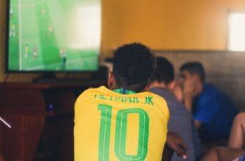 Un joven ve un partido de fútbol por televisión con una camiseta de la selección brasileña de fútbol con el nombre de Neymar.
