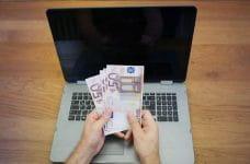 Billetes de 50 euros en frente de la pantalla de un ordenador portátil.