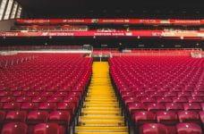Gradas vacías en un estadio con diversos carteles publicitarios.
