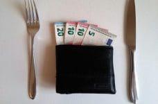 Cartera con billetes de euro entre un cuchillo y un tenedor.