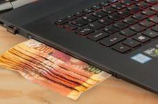 Billetes y ordenador portátil.