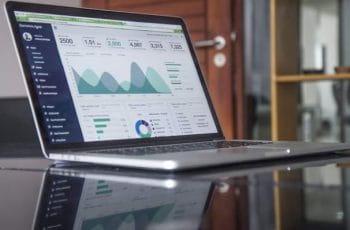 Ordenador portátil abierto con diversas gráficas en la pantalla.