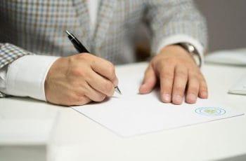Firma de un acuerdo o contrato.